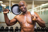 Shirtless muscular man holding frying pan in gym — Stock Photo