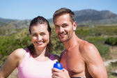 Active couple smiling at camera in the countryside — Foto Stock