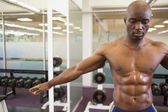 Serious shirtless muscular man in gym — Stock Photo