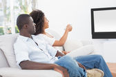 Couple sitting on couch together watching tv — Stock Photo