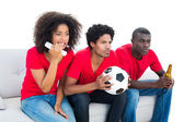 Nervous football fans in red sitting on couch — Stok fotoğraf