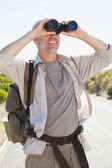 Hiker standing on road looking through binoculars — Stock Photo