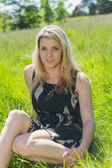 Hezká blondýnka v letní šaty, sedí na trávě — Stock fotografie