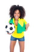 Pretty football fan holding brazilian flag cheering at camera  — Stock Photo