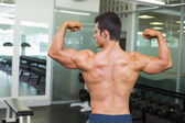 Rear view of a muscular man flexing muscles — Foto Stock