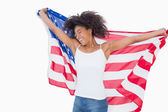 Pretty girl wrapped in american flag cheering — Stockfoto