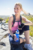 Cyclist taking break on rocky peak — Stock Photo