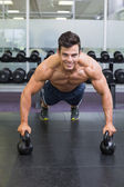 Muscular man doing push ups with kettle bells in gym — Stock Photo