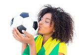 Pretty football fan with brazilian flag kissing ball — Stock Photo