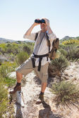 Hiker looking through binoculars on country trail — Photo