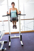 Fit brunette supporting her weight on bars — Stock Photo