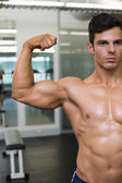 Muscular man flexing muscles in gym — Stockfoto