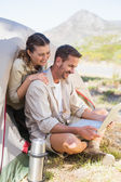Outdoorsy couple looking at the laptop outside tent — Stock Photo