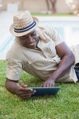 Smiling man relaxing in his garden using tablet pc — Stock Photo