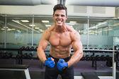 Shirtless muscular man flexing muscles in gym — Stockfoto