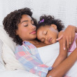 Cute daughter sleeping with mother on the sofa — Stock Photo #50060609