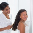Pretty mother brushing her daughters hair — Stock Photo