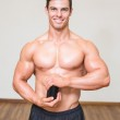 Body builder holding bottle with supplements in gym — Stock Photo #50061093