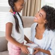 Pretty mother offering daughter a gift — Stock Photo #50061437
