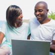 Happy couple sitting in garden using laptop together — Stock Photo #50061575