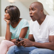 Bored woman sitting next to her boyfriend playing video games — Stock Photo #50062007