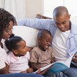 Happy family sitting on couch together reading book — Stock Photo #50062861