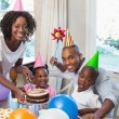 Happy family celebrating a birthday together at table — Stock Photo #50062865