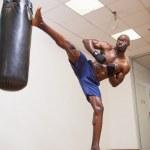 Muscular boxer kicking punching bag in gym — Stock Photo #50063381