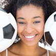 Pretty girl with afro hairstyle smiling at camera holding footba — Stock Photo #50063521