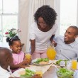 Mother serving juice to her family at lunch — Stock Photo #50064137
