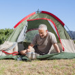 Happy camper cooking on camping stove outside his tent — Stock Photo #50064279