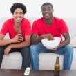 Football fans in red sitting on couch with beer and popcorn — Stock Photo #50064307