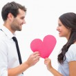 Hipster couple smiling at camera holding a heart — Stock Photo #50064371