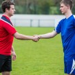 Football players in blue and red shaking hands — Stock Photo #50064607