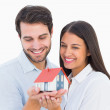 Attractive young couple holding a model house — Stock Photo #50065007