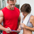Handsome personal trainer with his client looking at clipboard — Stock Photo #50065075