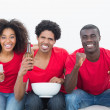 Football fans in red sitting on couch with beer and popcorn — Stock Photo #50065099