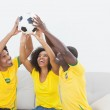 Brazil football fans sitting on couch holding ball — Stock Photo #50065151