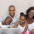 Happy family using laptop together on bed — Stock Photo #50065183