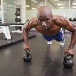 Muscular man doing push ups in gym — Stock Photo #50065657