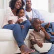 Happy family sitting on couch together watching tv — Stock Photo #50065819