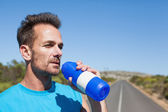 Athletic man on open road taking a drink — Stock Photo