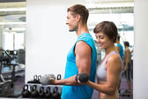 Fit happy couple lifting dumbbells together — Foto Stock