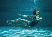 Athletic swimmer smiling at camera underwater — Stock Photo