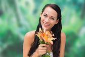 Beautiful nude brunette smelling bunch of lilies — Stock Photo