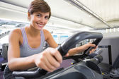 Smiling brunette working out on the cross trainer — Stockfoto