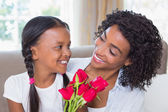 Pretty mother with her daughter holding roses — Stockfoto