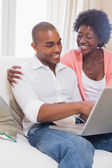 Cute couple relaxing on couch with laptop — Stock Photo