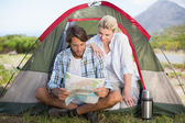 Couple sitting by their tent reading map — Stock Photo
