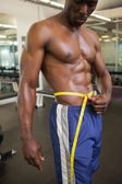 Muscular man measuring waist in gym — Stock Photo